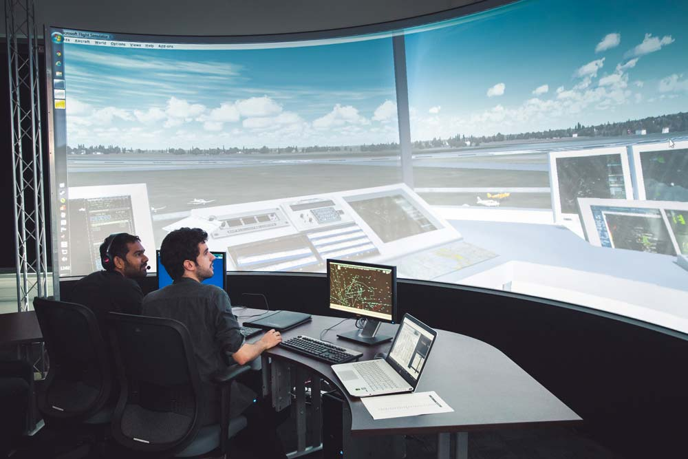Air traffic management lab students working in front of lit screen landscape
